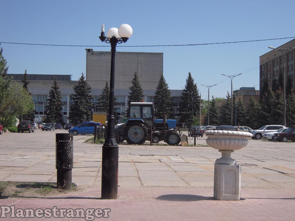 Композиция с трактором, разбитым фонарём и осколком советских декораций